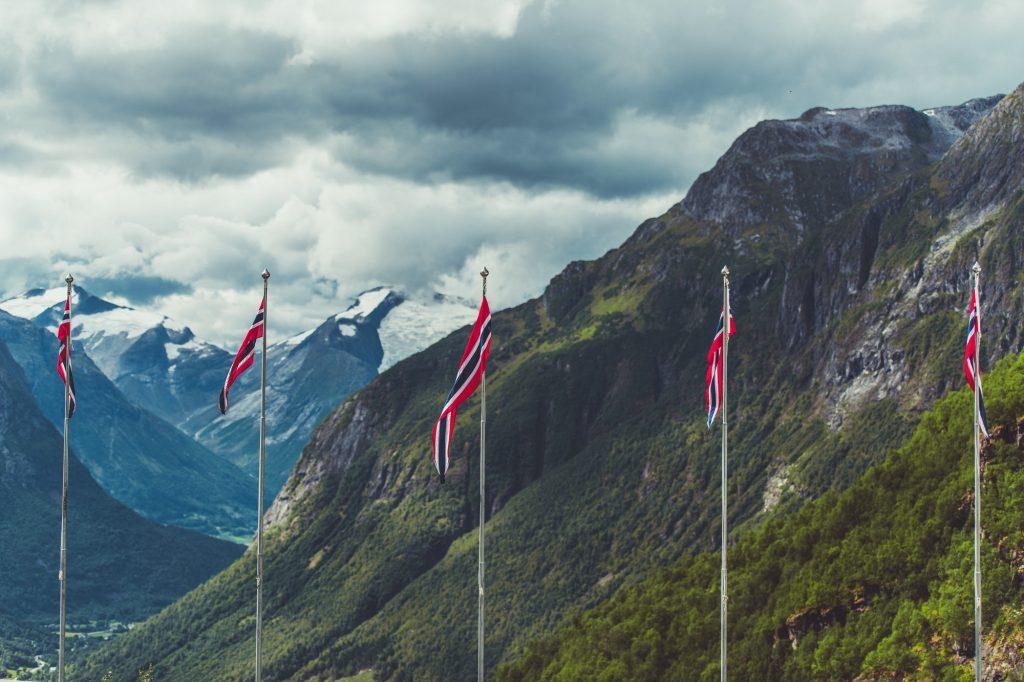 Norske flagg med fjell i bakgrunnen
